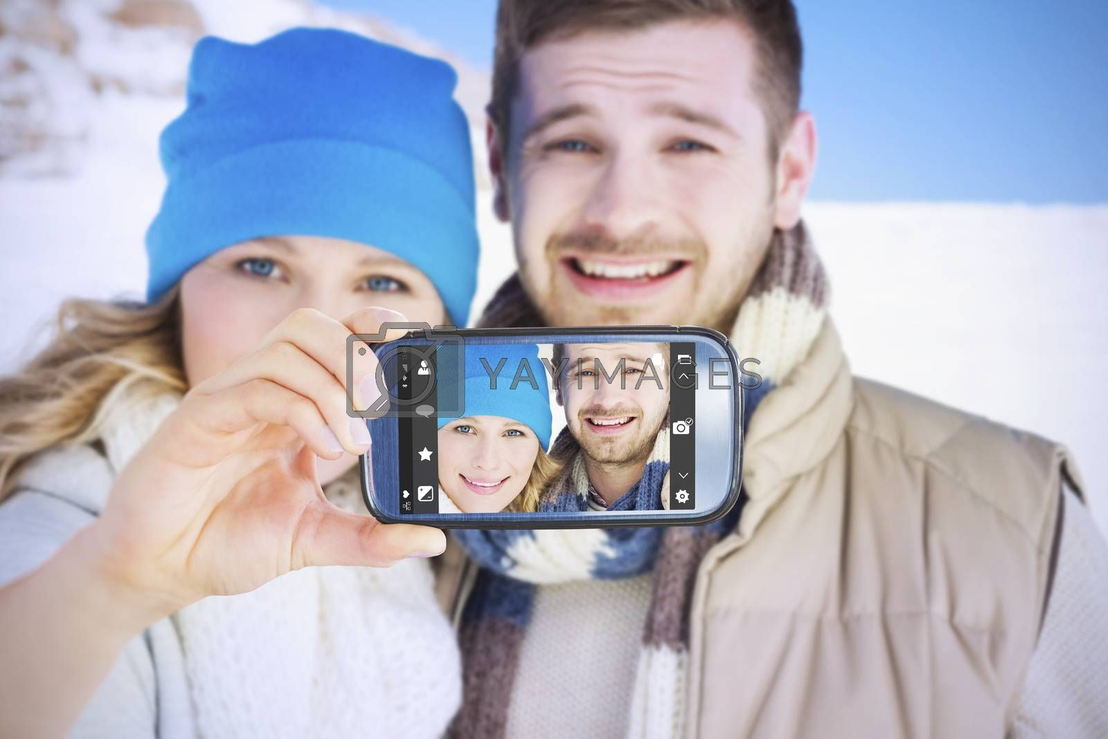 Hand holding smartphone showing against couple in warm clothing on snow covered landscape