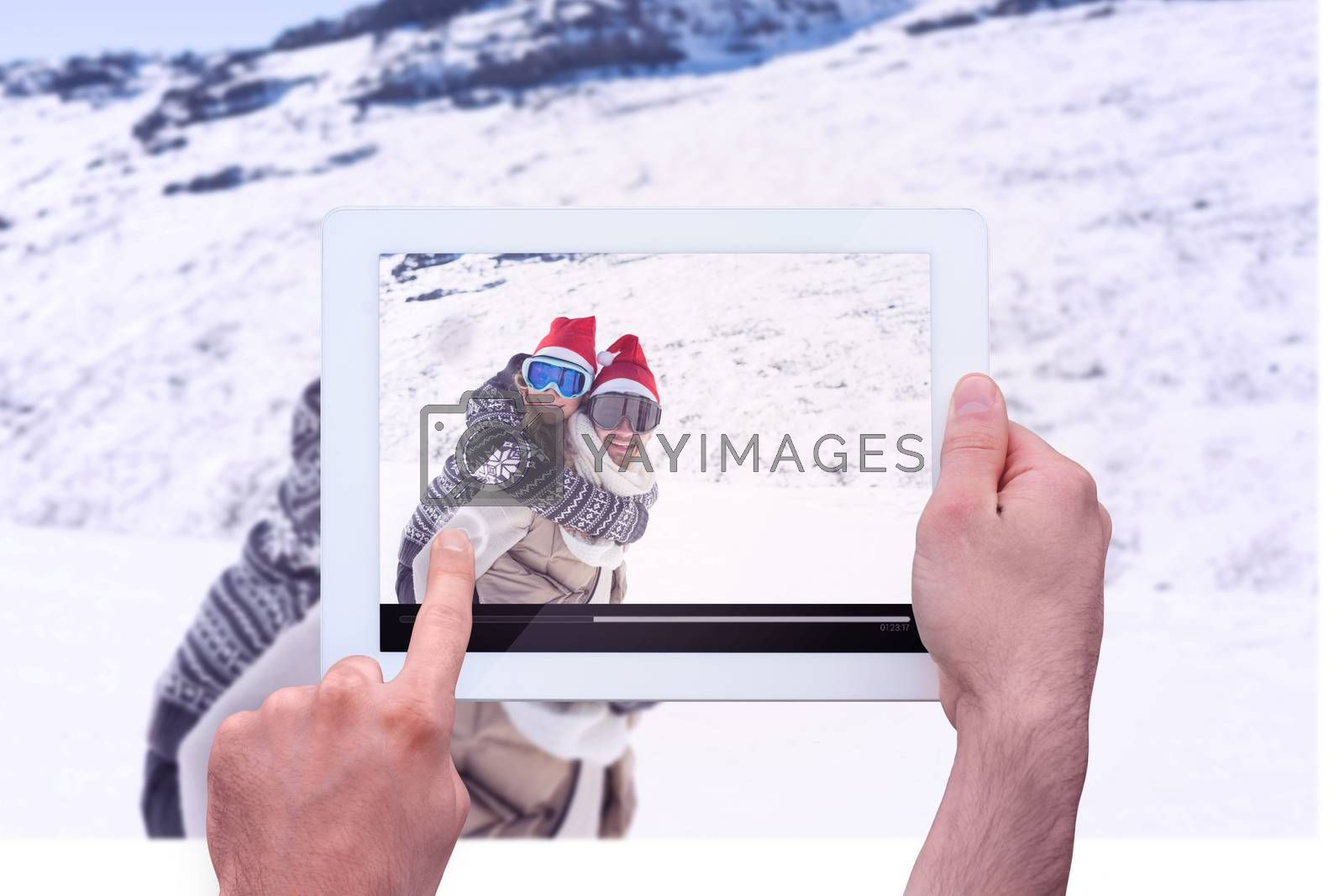 Hand holding tablet pc against man piggybacking cheerful woman on snow