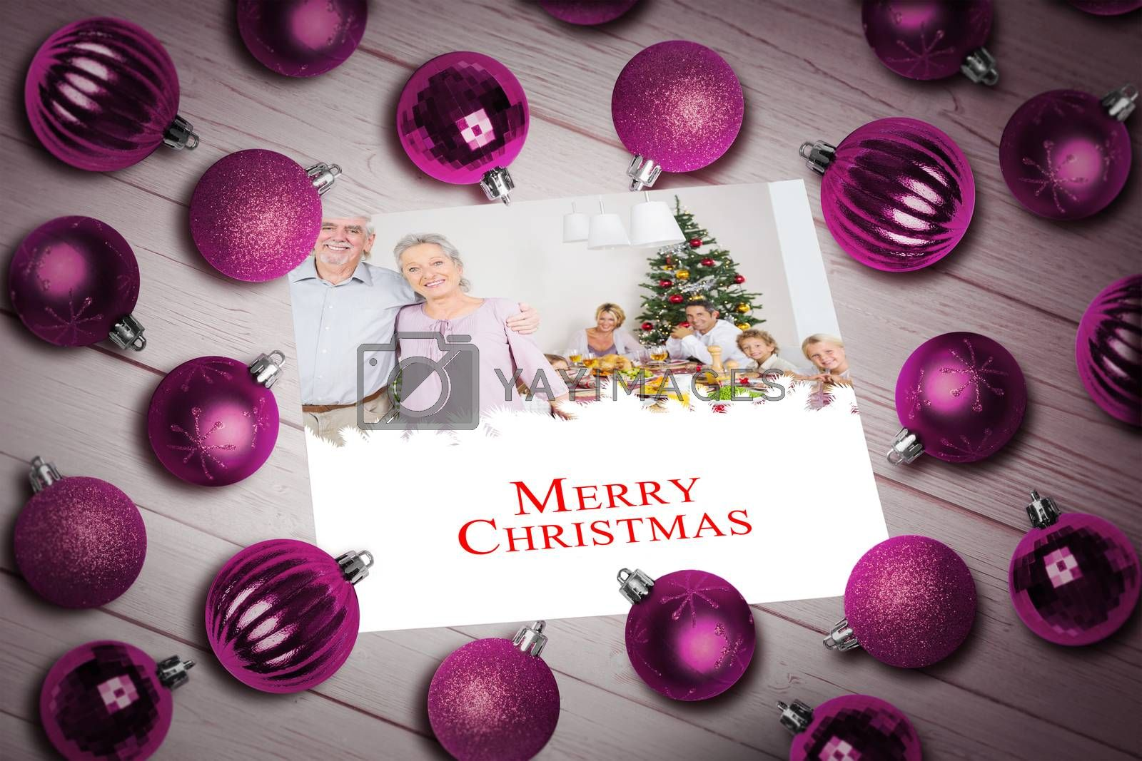 Christmas baubles on table against a happy family christmas card