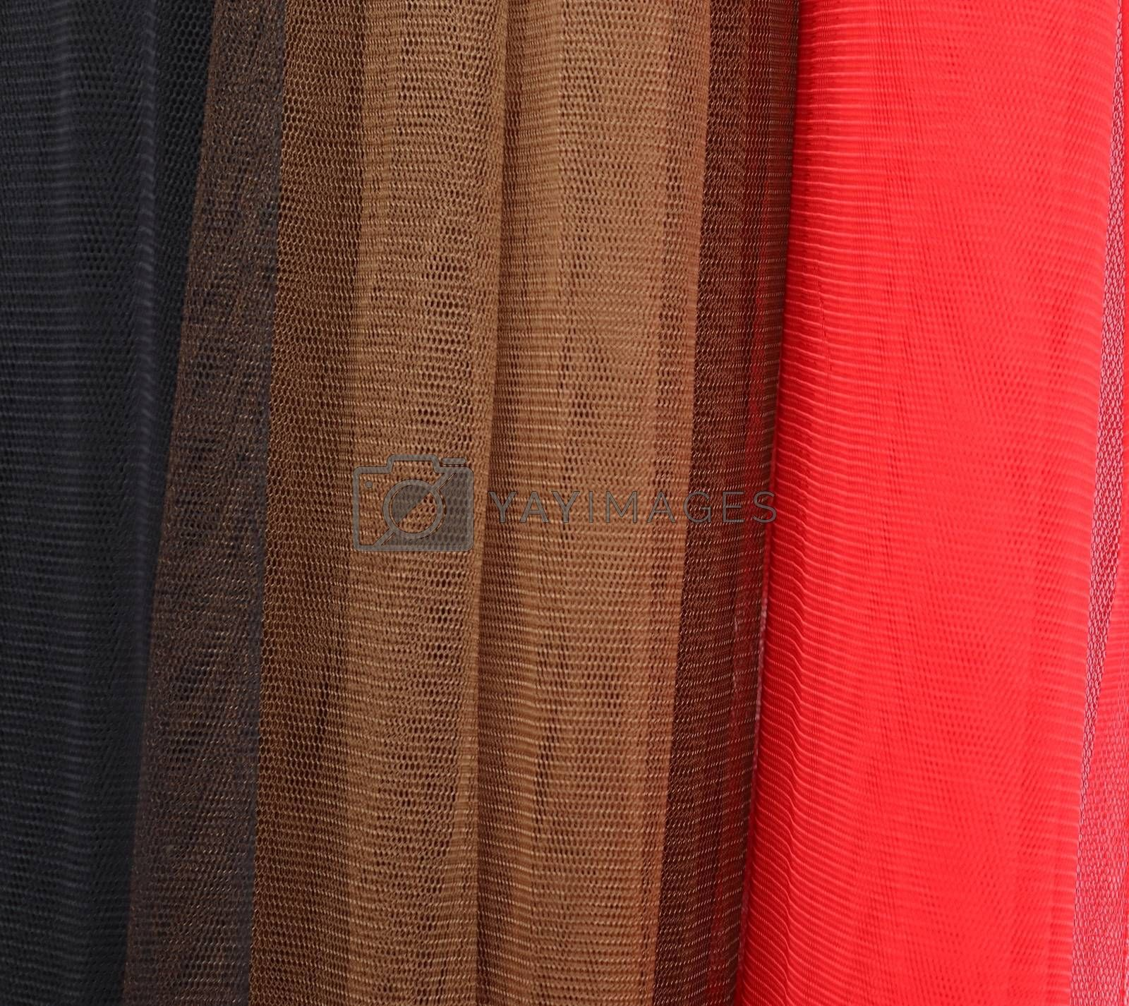 Detailed close up view on samples of cloth and fabrics in different colors found at a fabrics market.