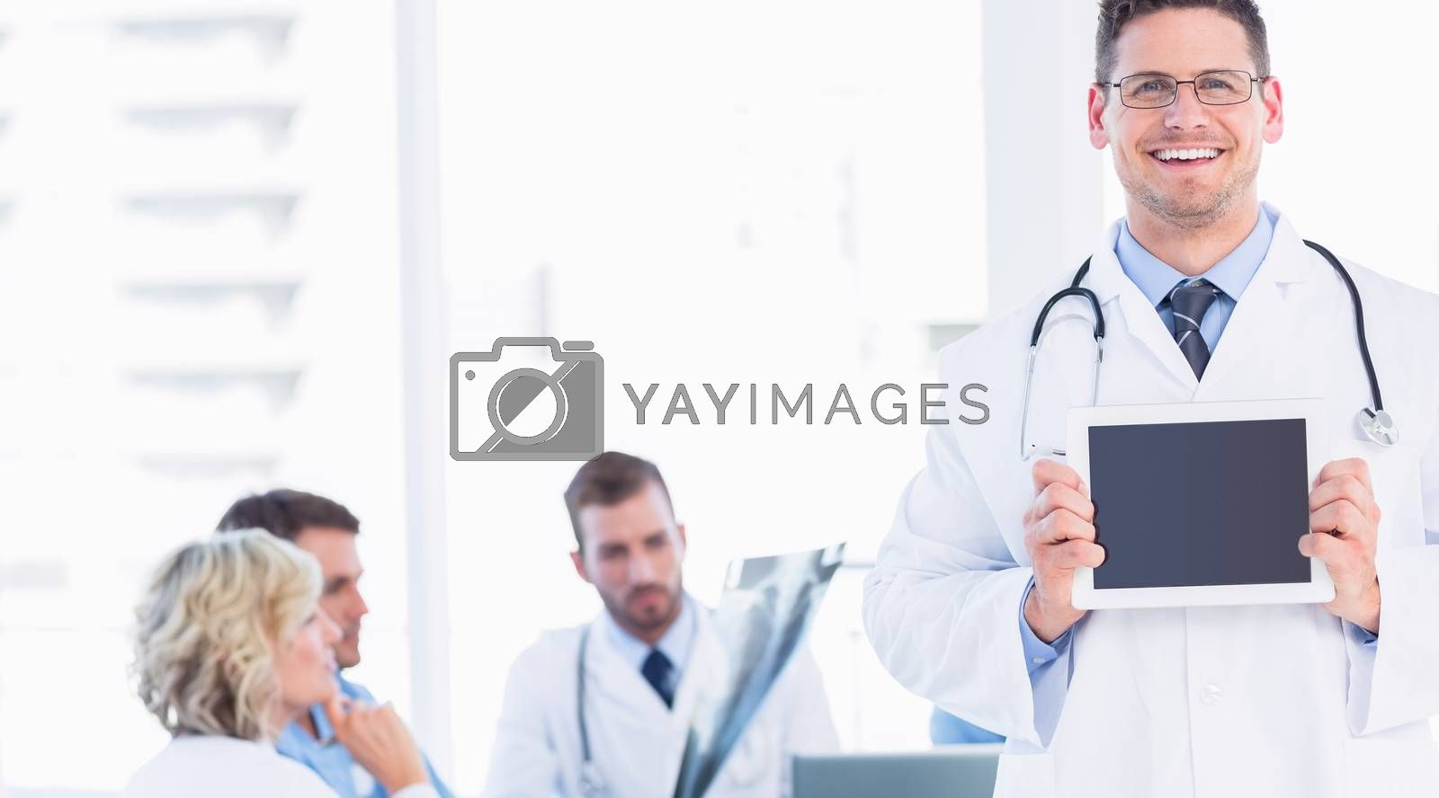 Doctor holding digital tablet with colleagues in meeting at a medical office