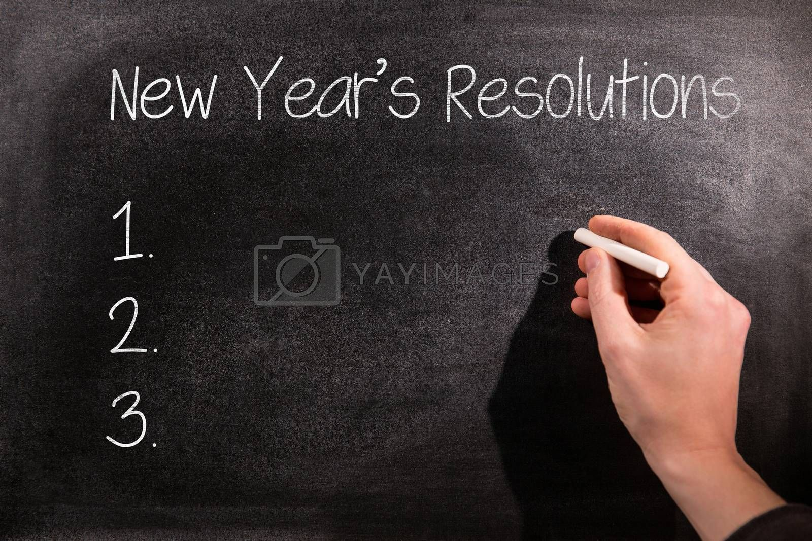 New years resolution list against man drawing on chalkboard