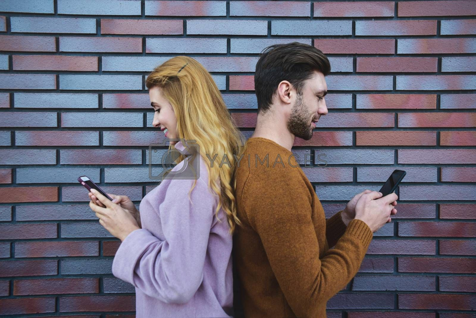 Side portrait of beautiful young couple is using smartphones and smiling, standing back to back against brown brick wall.