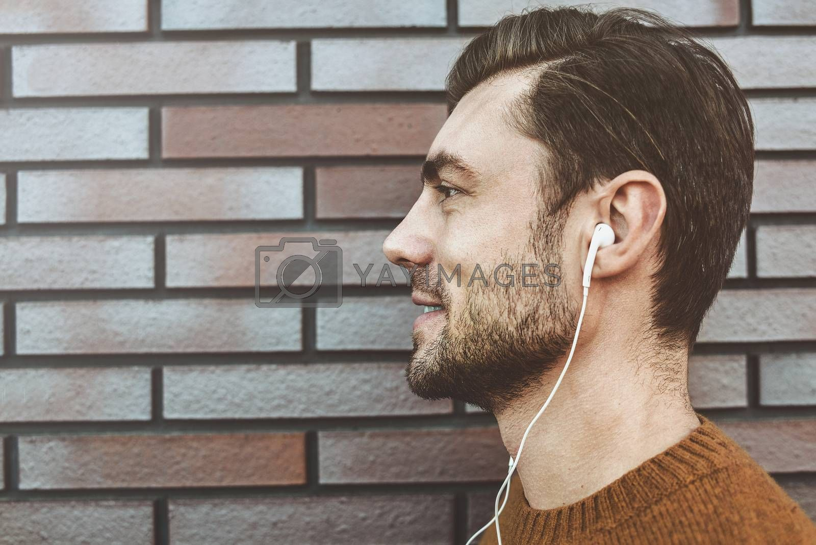 Photo of stylish handsome young man with bristle standing outdoors. Man wearing brown sweater. Smiling man listening to music on headphones and leaning against brick wall.