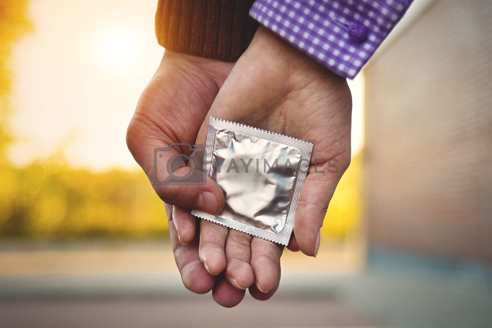 Men, women, couples Holding a condom for self-protection. Concept to prevent contraception.