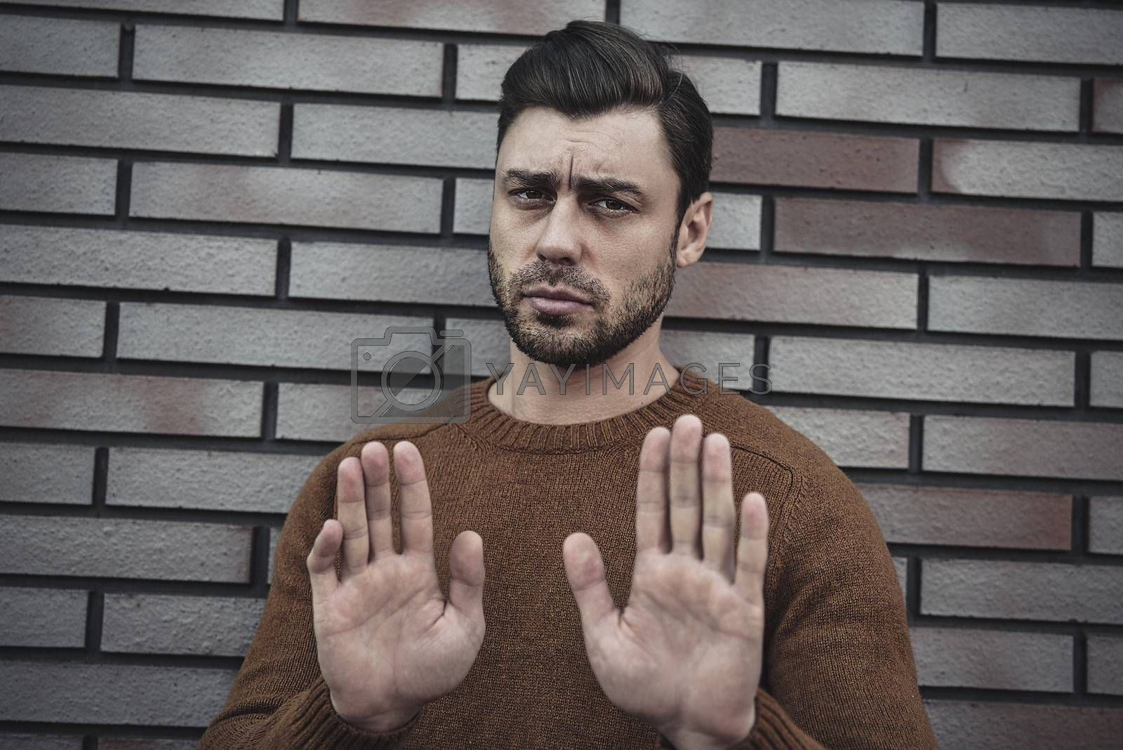 Young caucasian man standing on brick wall background afraid and terrified with fear expression stop gesture with hands, shouting in shock. Panic concept.