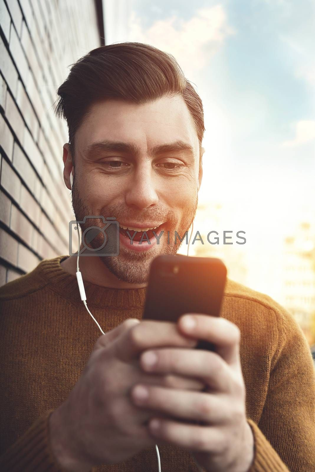 Smiling man listening to music on headphones and leaning against brick wall. Portrait of smiling man with headphones and cellphone standing by brick wall.