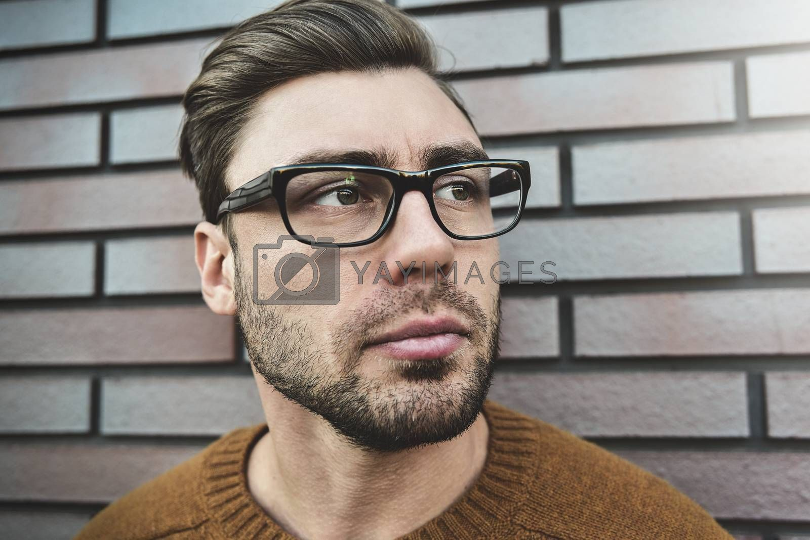 Portrait of serious manly stunning man in glasses and sweater looking at camera standing on street.