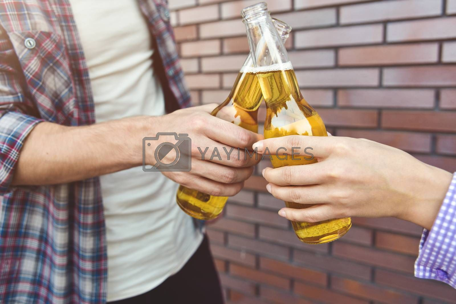 Friends enjoying with beer on a brown brick wall background.