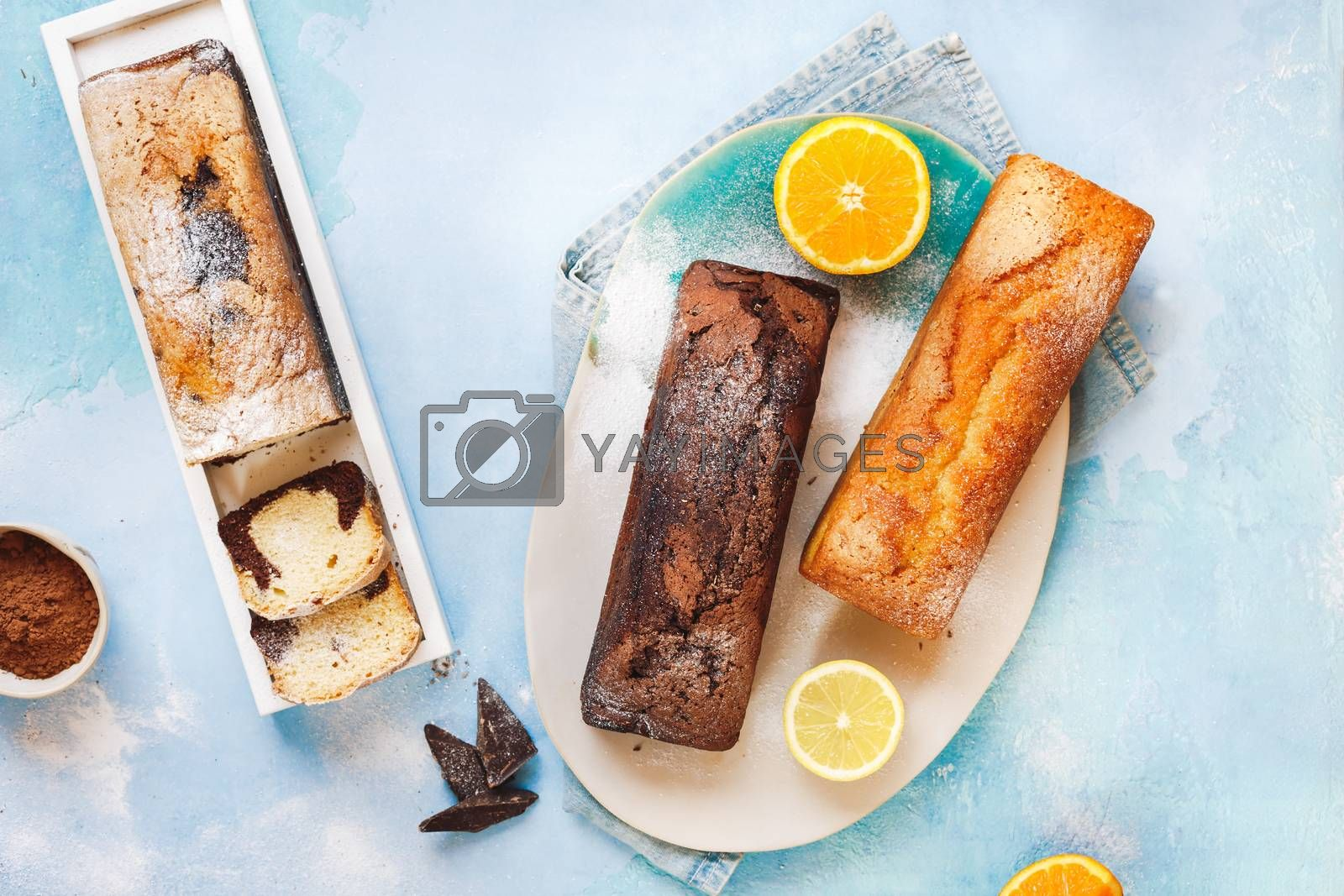 Assorted pound cakes whole and sliced into portions lying on a coloured rustic table, top view, blank space