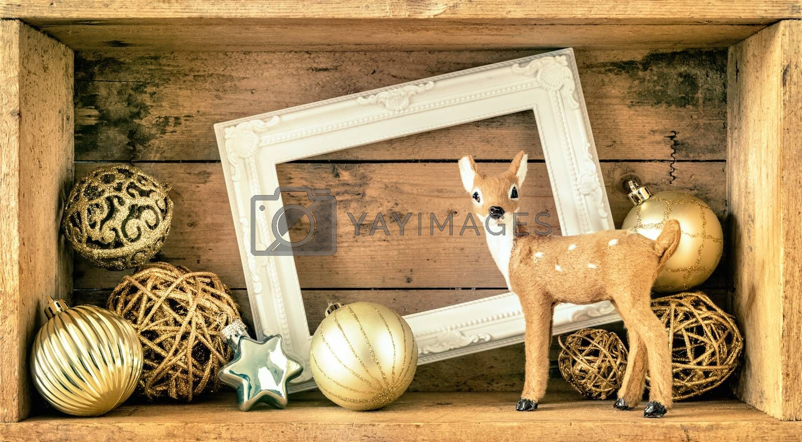 An image of a Christmas decoration wooden box with deer golden balls and a white frame