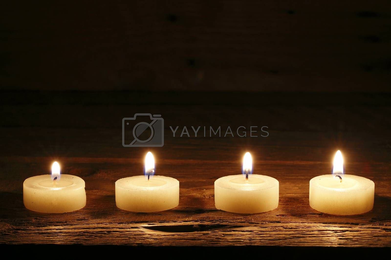 four burning candles on wood