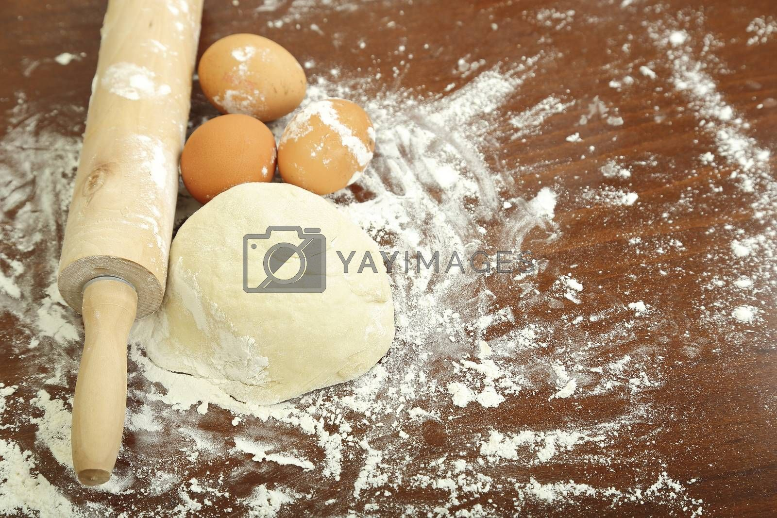 dough with flour, rolling pin and eggs on wooden surface