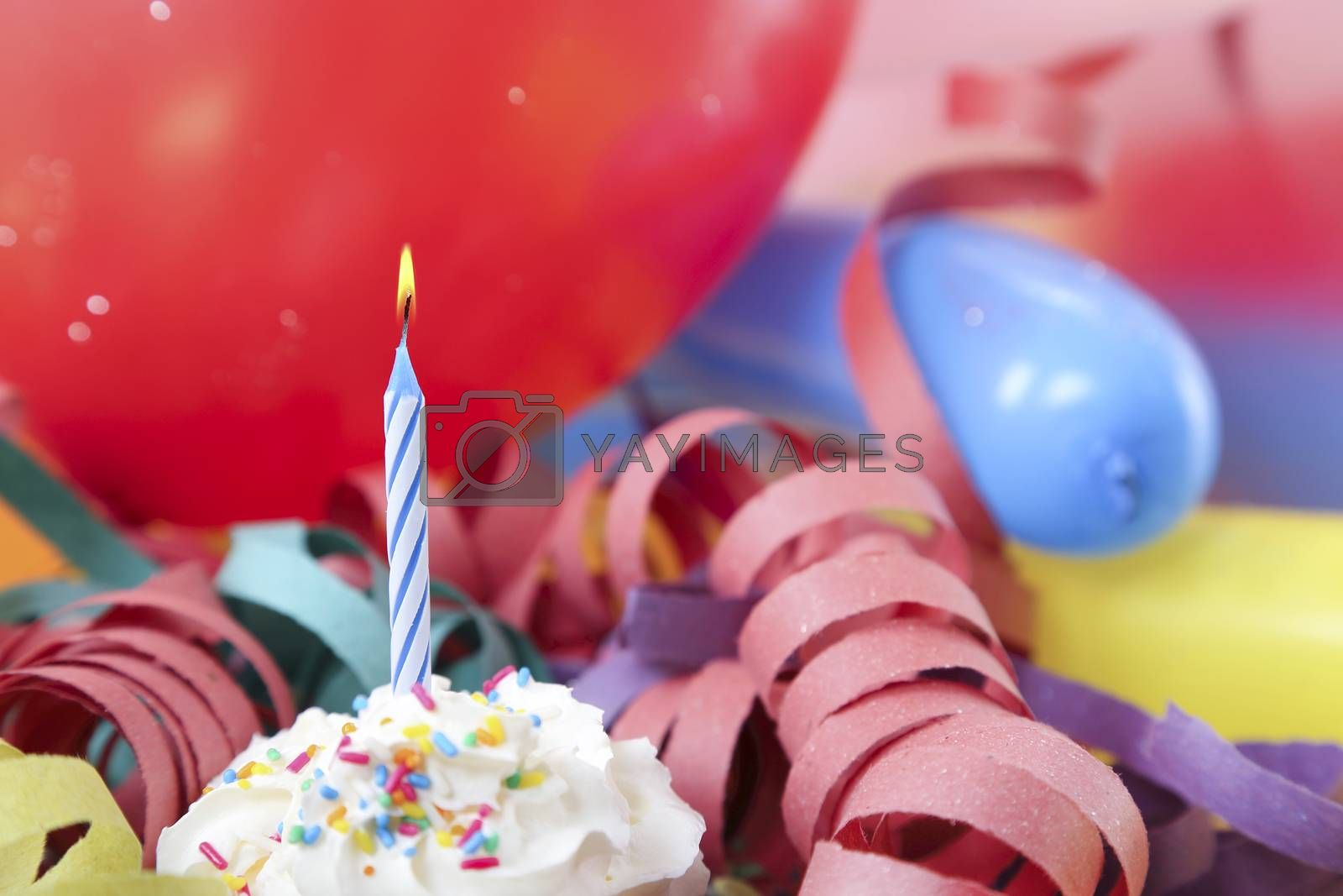 blue birthday candle in front of balloons and streamers