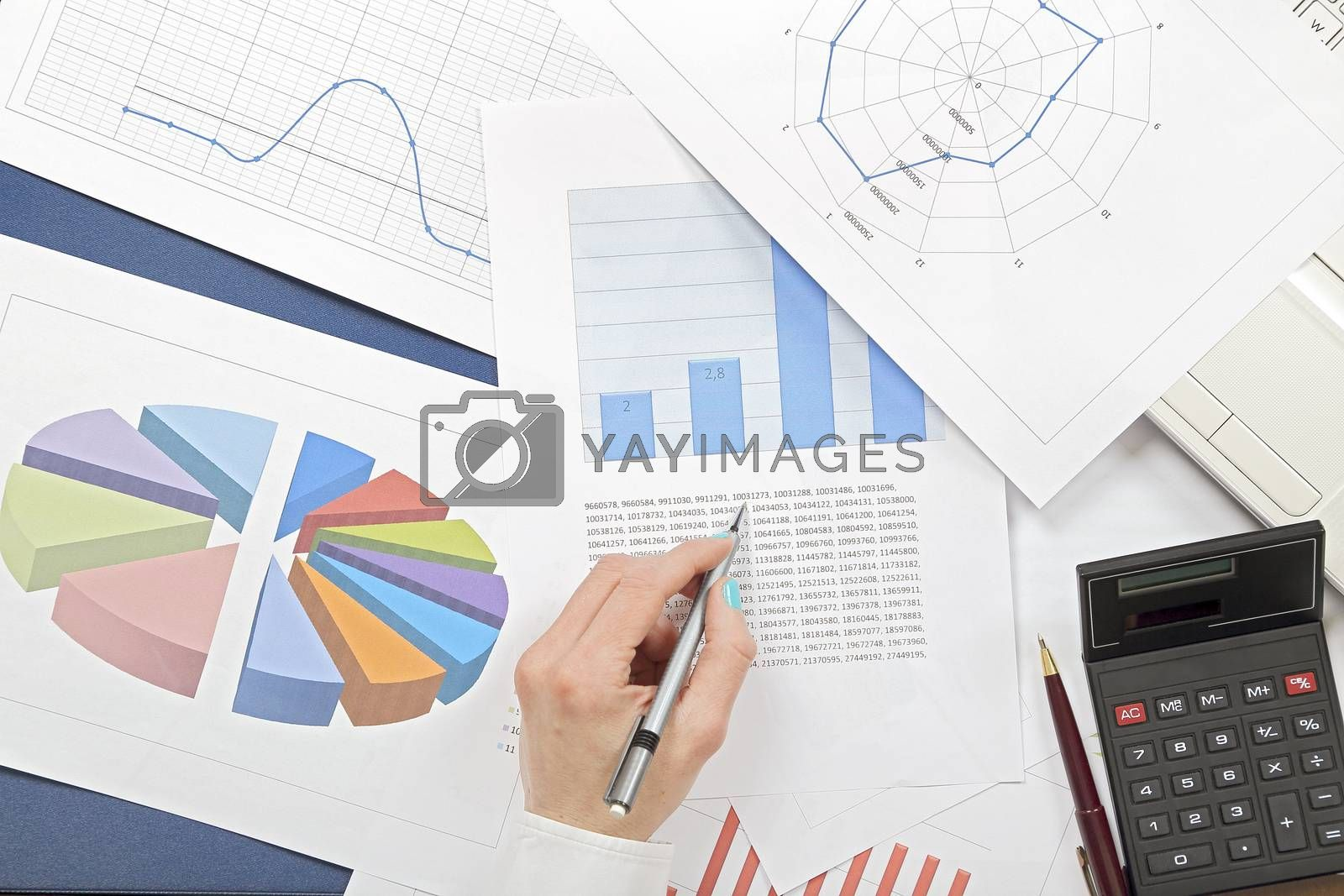 woman's hand over pages with stats