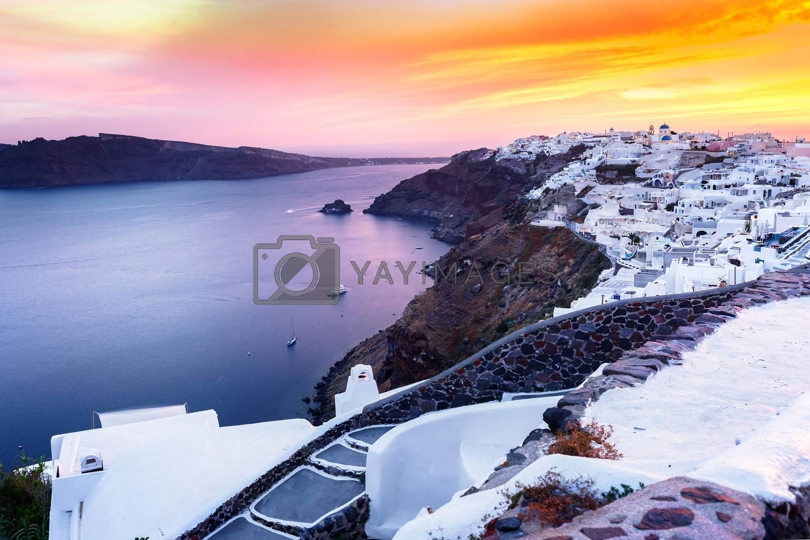 World famous Oia village at sunset, Santorini.  Caldera and traditional, famous white washed buildings and churches with blue domes over the caldera,Santorini island, Greece.