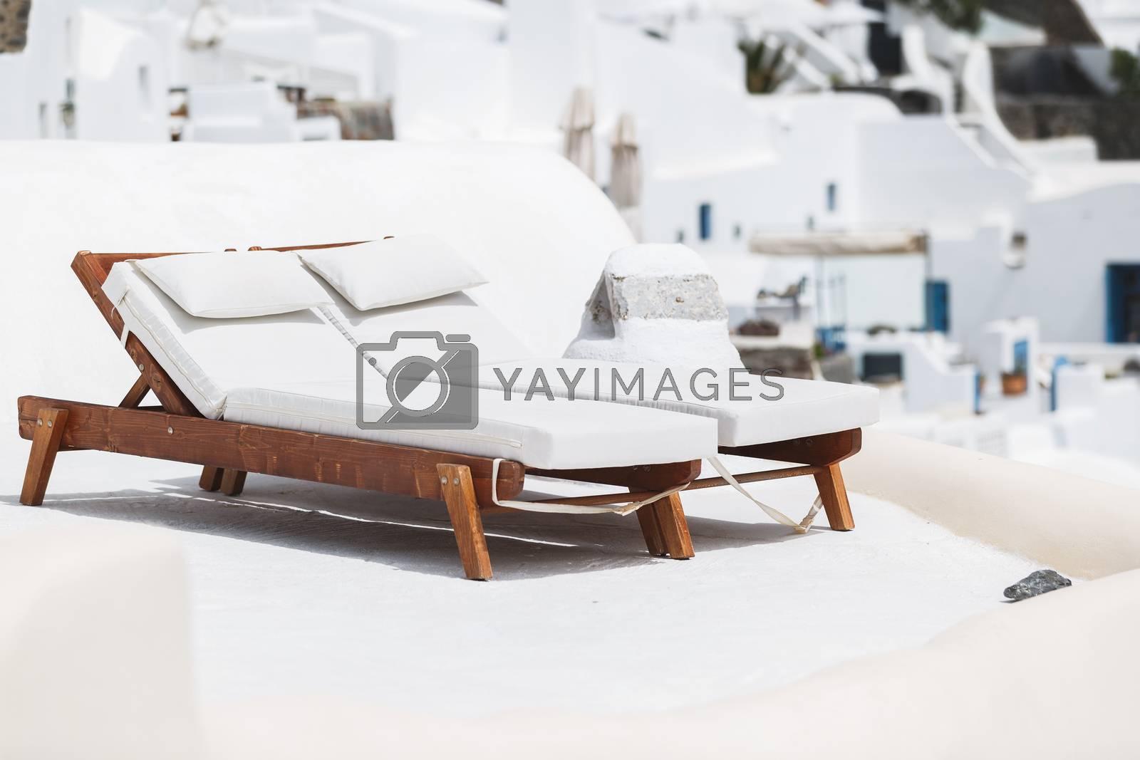 Two sun beds on traditional terrace. Santorini island, Greece