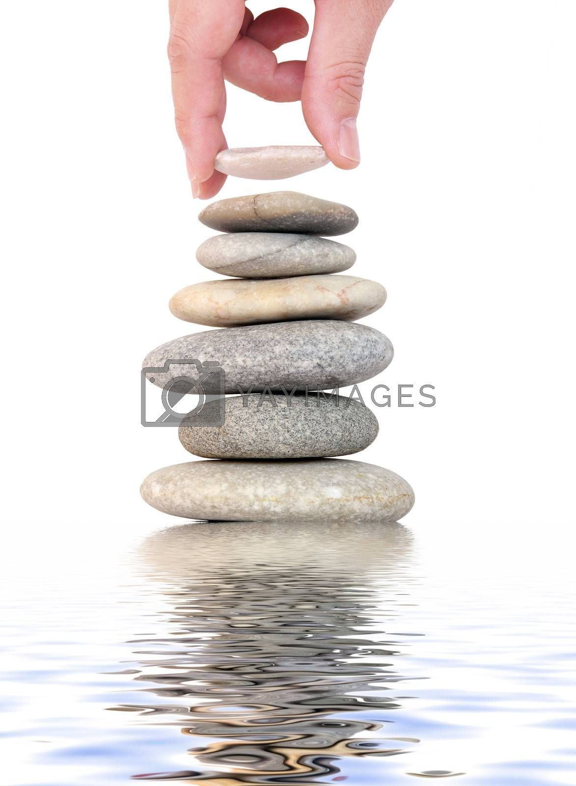 placing the last stone on stone stack with water reflection