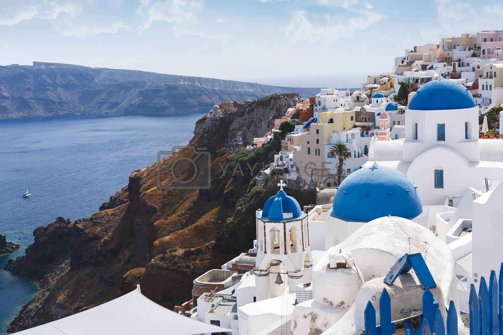Blue domes and bell tower of churches in Oia, Santorini, Greece.  The edge of the caldera with the blue domes of churches in the foreground, selective focus