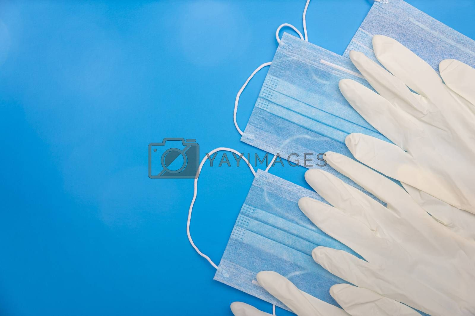 flat lay image of surgical gloves and disposable medical face masks for prevent infection on classic blue background