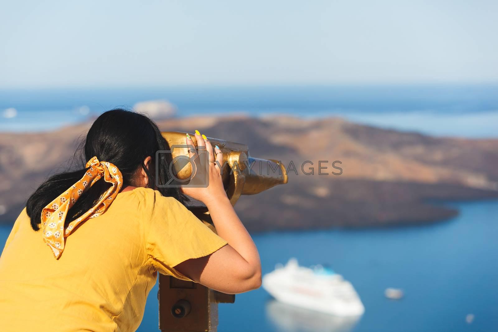 Beautiful young woman looking at cruise ships with binoculars in Thira, Santorini, Greece  enjoying vacation, selective focus