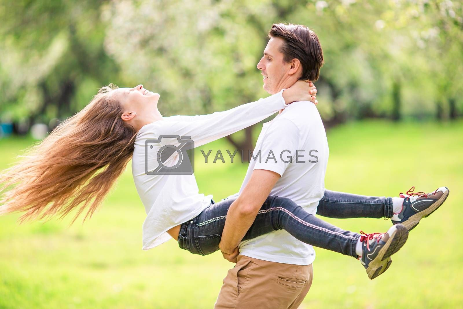 Family of dad and daughter with long hair having fun outdoors in the park