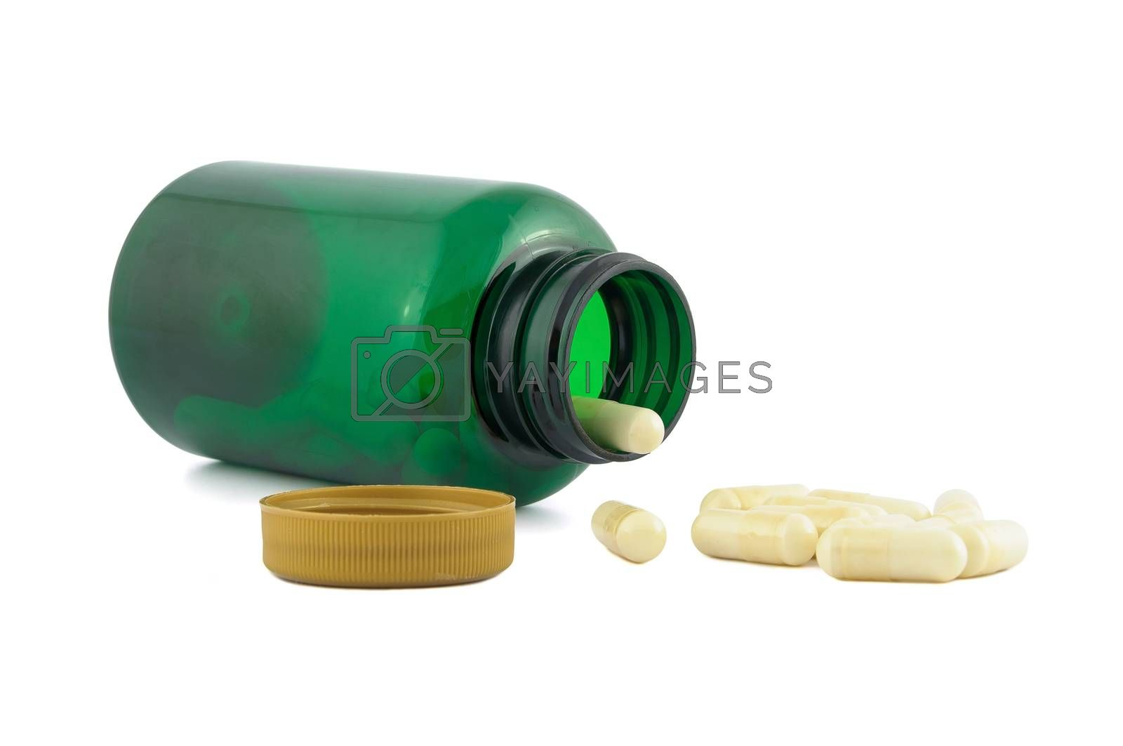 Pills falling out from green jar isolated on white background with clipping path