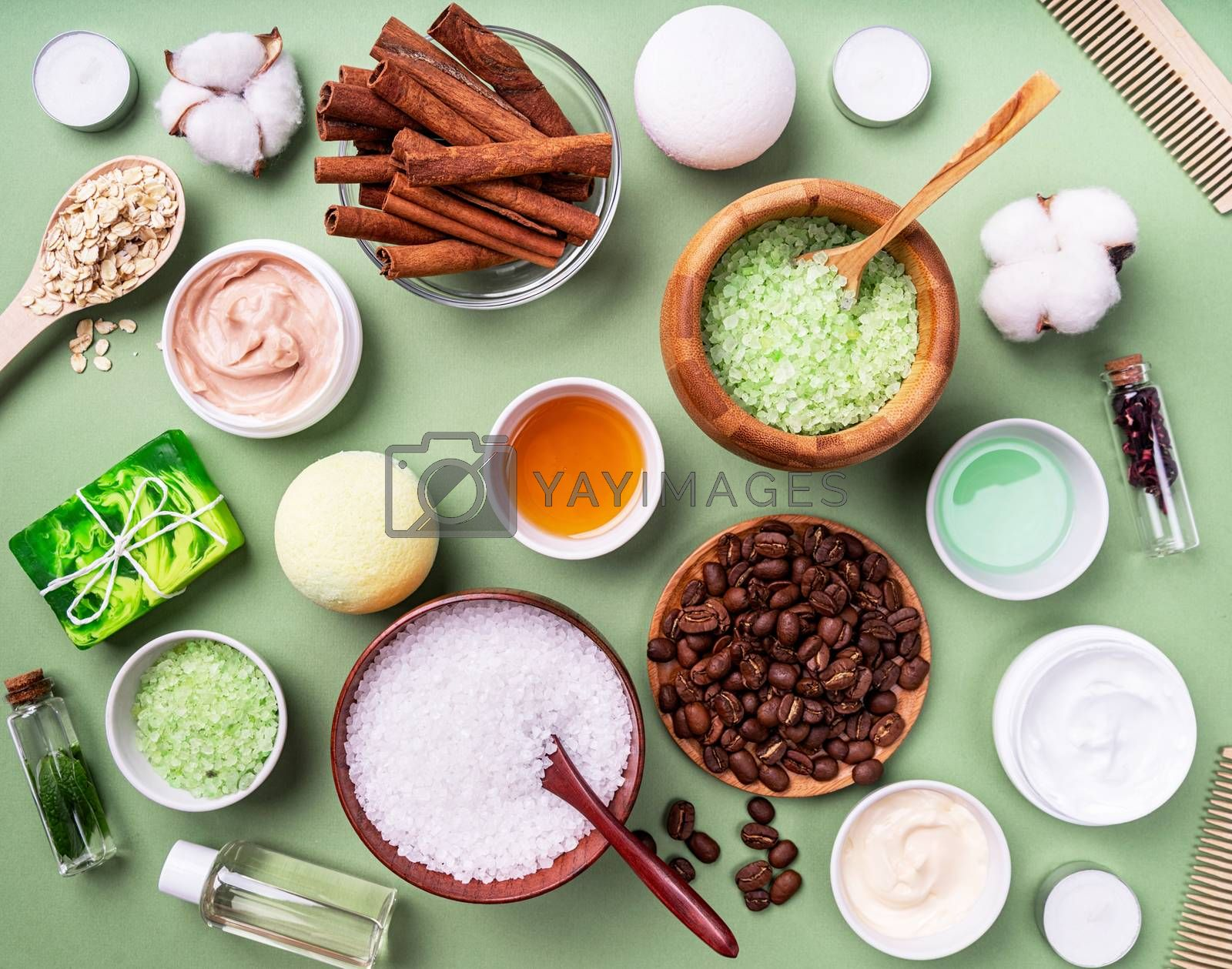Natural cosmetics and spa ingredients top view on green background