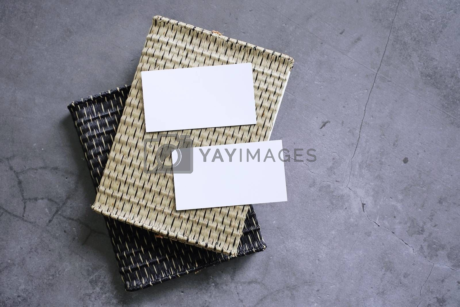 Flat lay branding identity business name card on wicker book cover in modern style on dark stone background, minimal concept for design