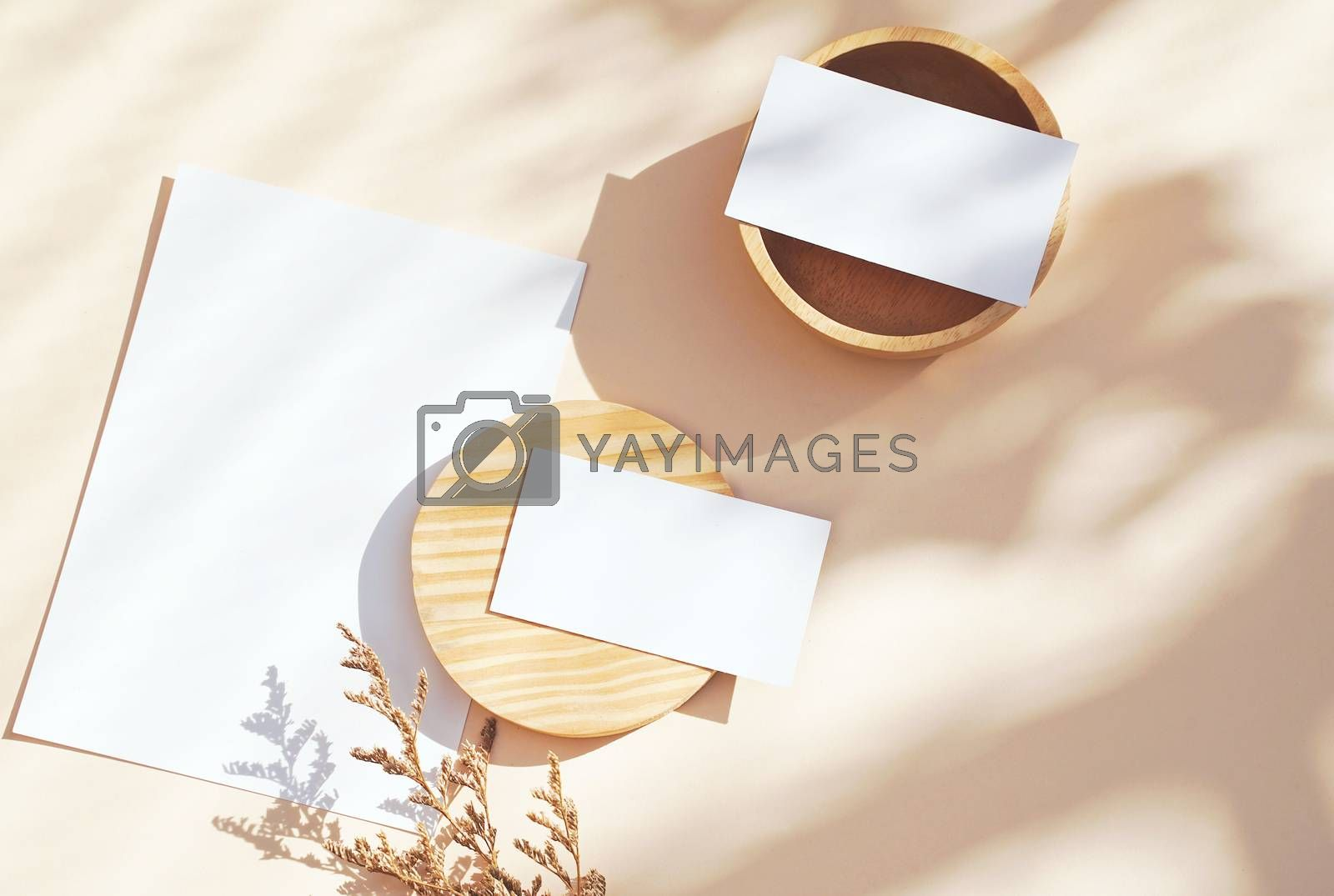 Flat lay of branding identity business name card on yellow background with flower and wooden container, light and shadow shape leaves, minimal concept for design