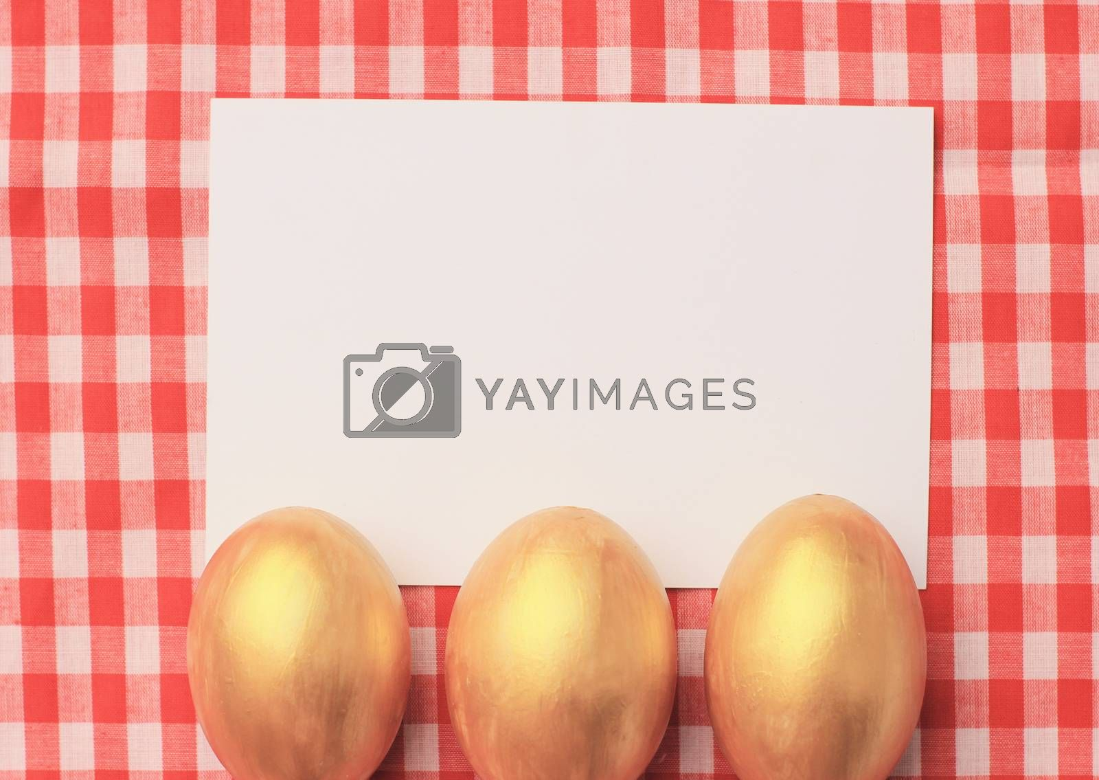 Royalty free image of Golden easter eggs on red checkered tablecloth background with b by nuchylee