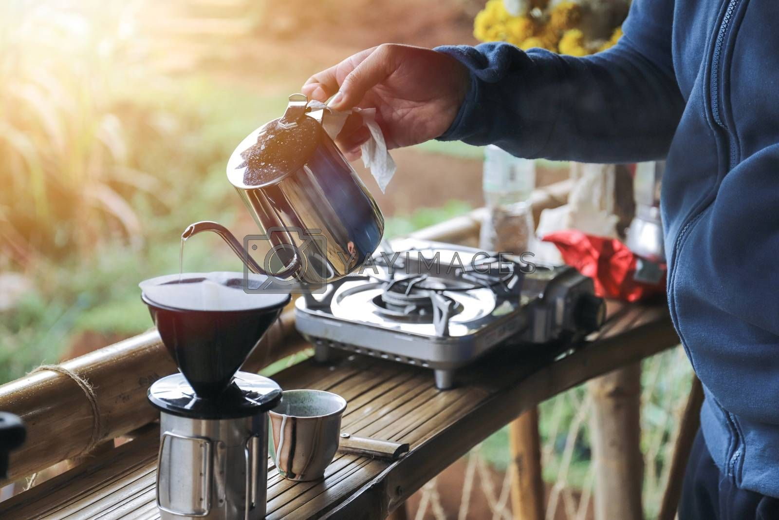 Royalty free image of close up hands drip coffee with morning light  by nuchylee