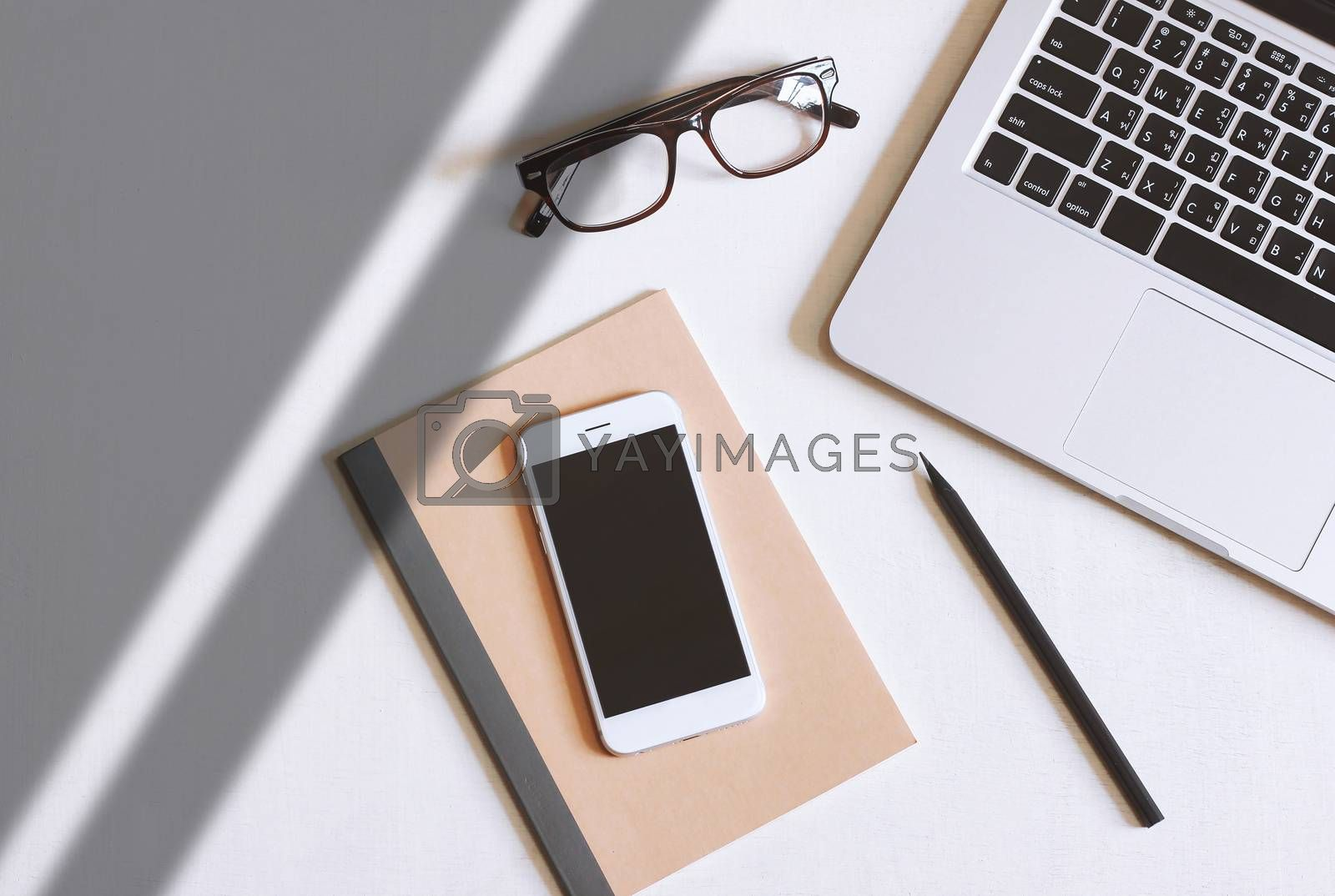 Royalty free image of Flat lay photo of office desk with laptop, smartphone, eyeglasse by nuchylee