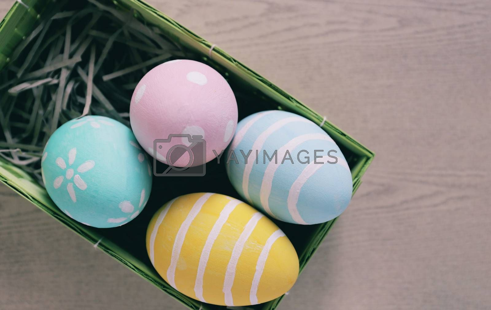 Royalty free image of Pastel and colorful easter eggs in nest and basket on wooden bac by nuchylee