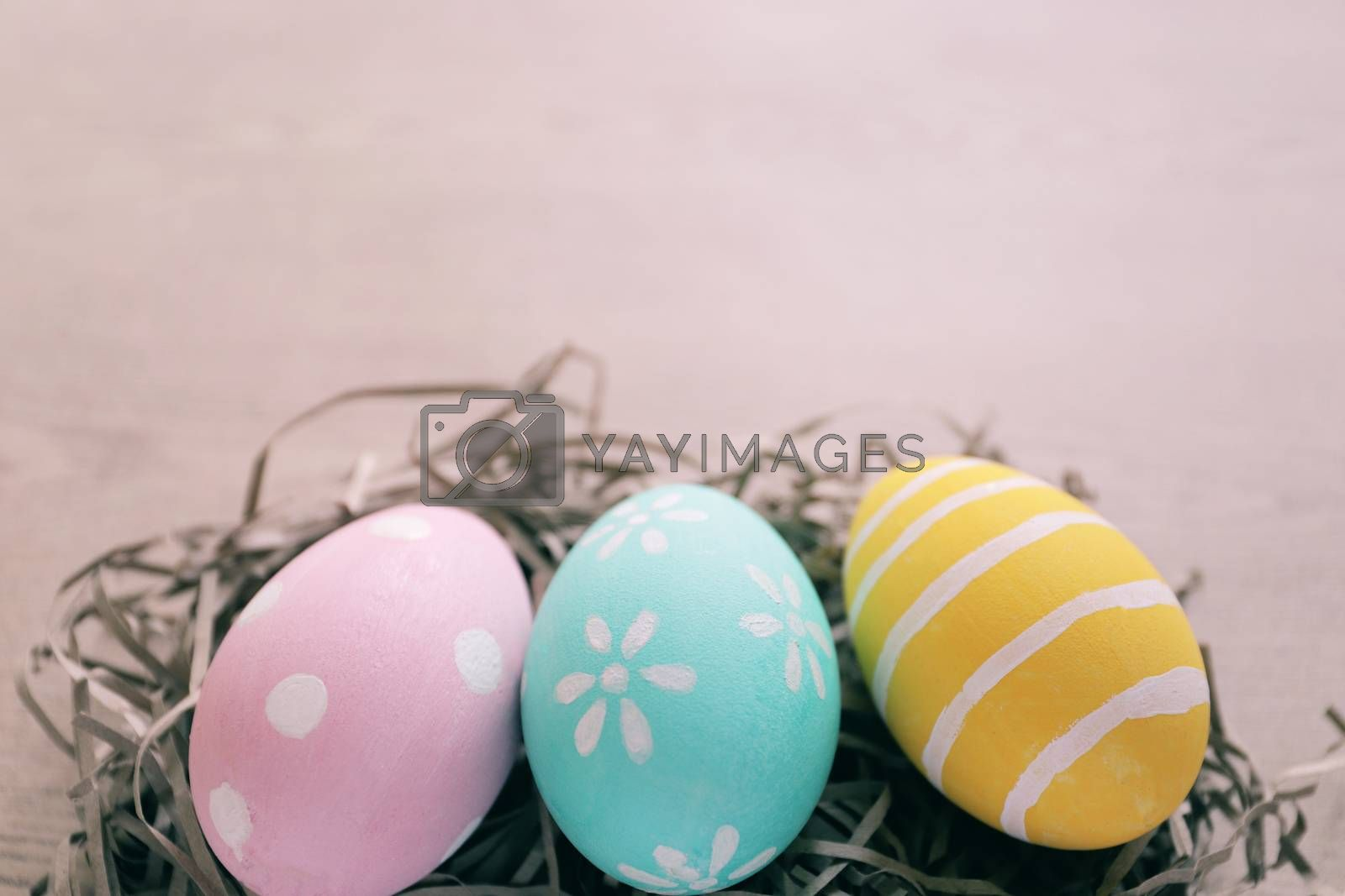 Royalty free image of Pastel and colorful easter eggs on nest with wooden background a by nuchylee