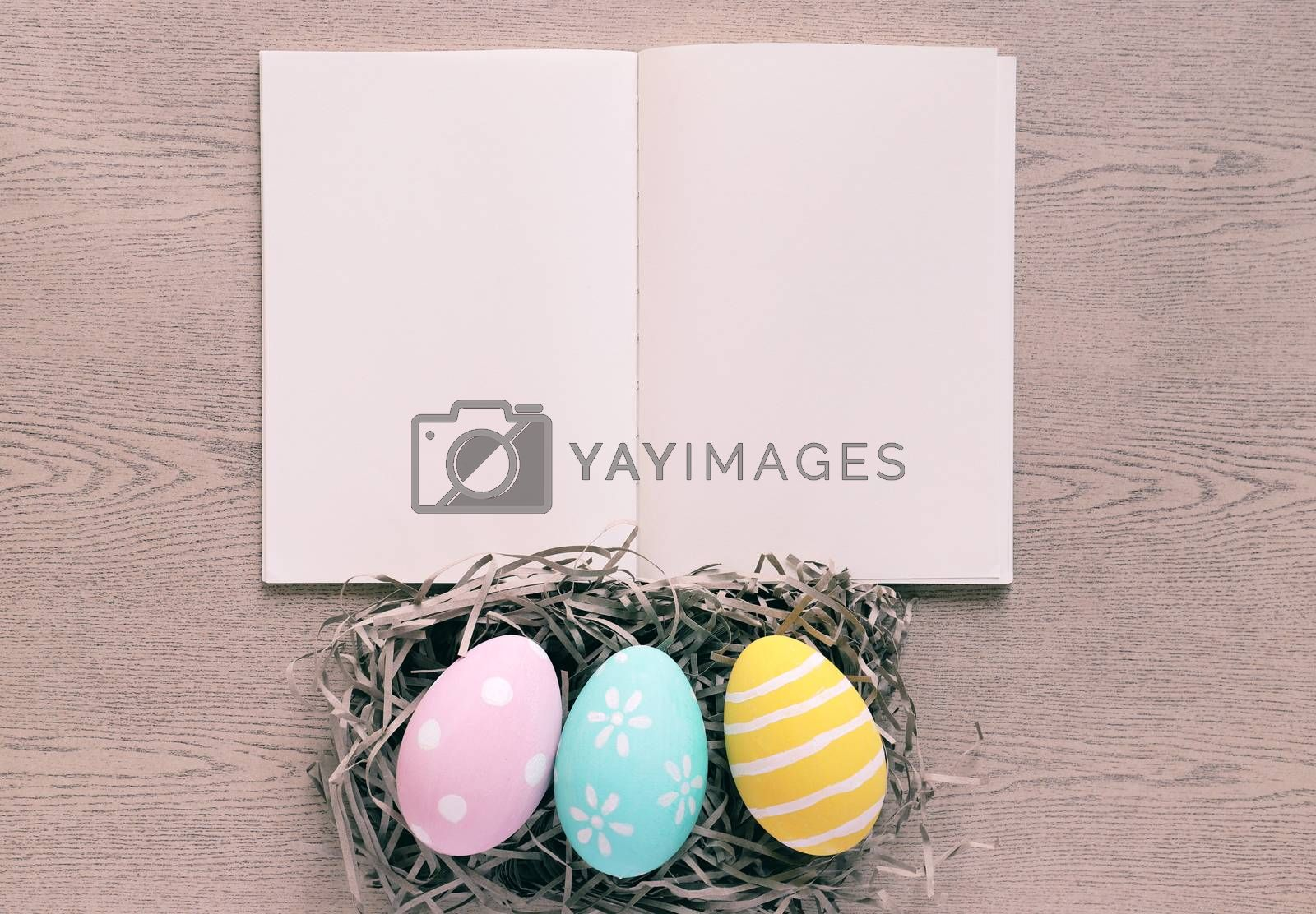 Royalty free image of Pastel and colorful easter eggs on nest with blank notebook on w by nuchylee