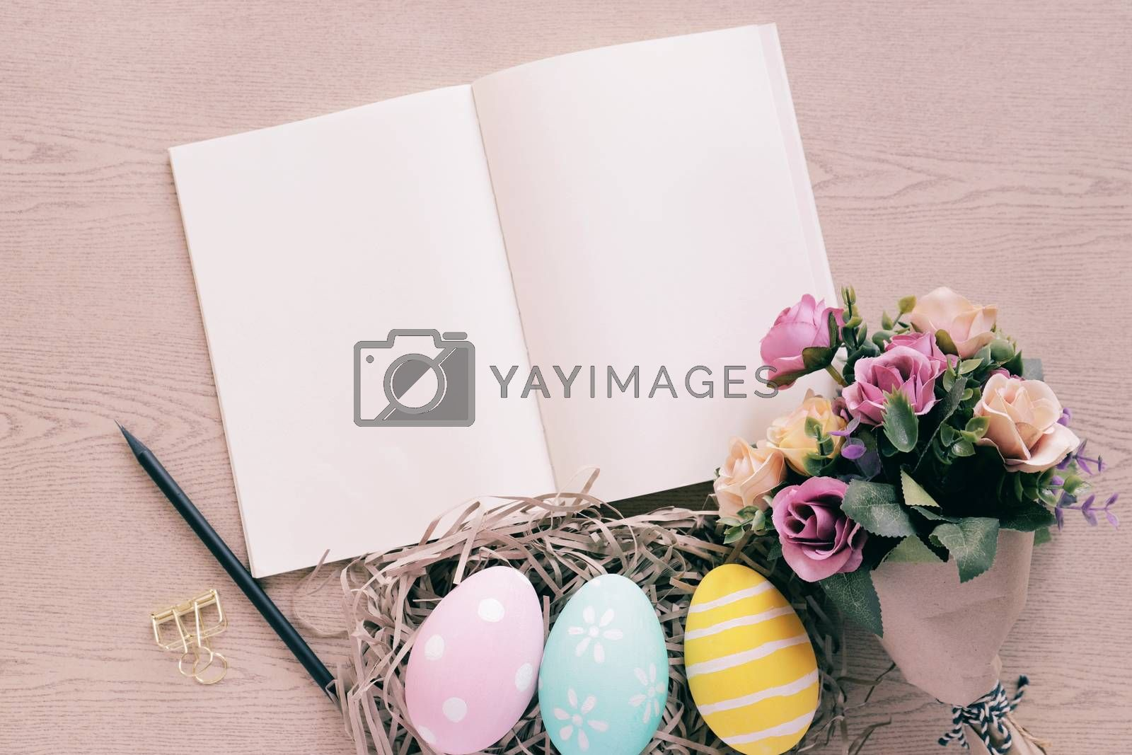 Pastel and colorful easter eggs in nest and bouquet of flower with blank notebook on wooden background, happy easter holiday concept