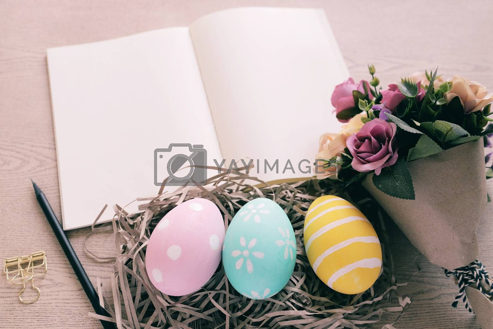Royalty free image of Pastel and colorful easter eggs in nest and bouquet of flower wi by nuchylee