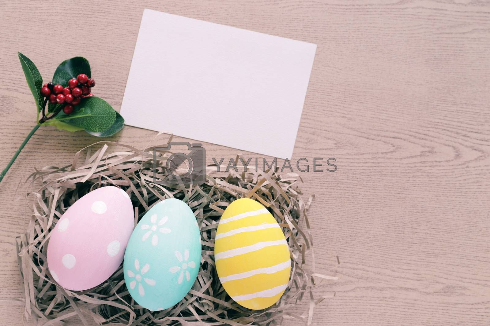 Royalty free image of Pastel and colorful easter eggs in nest with blank card on woode by nuchylee