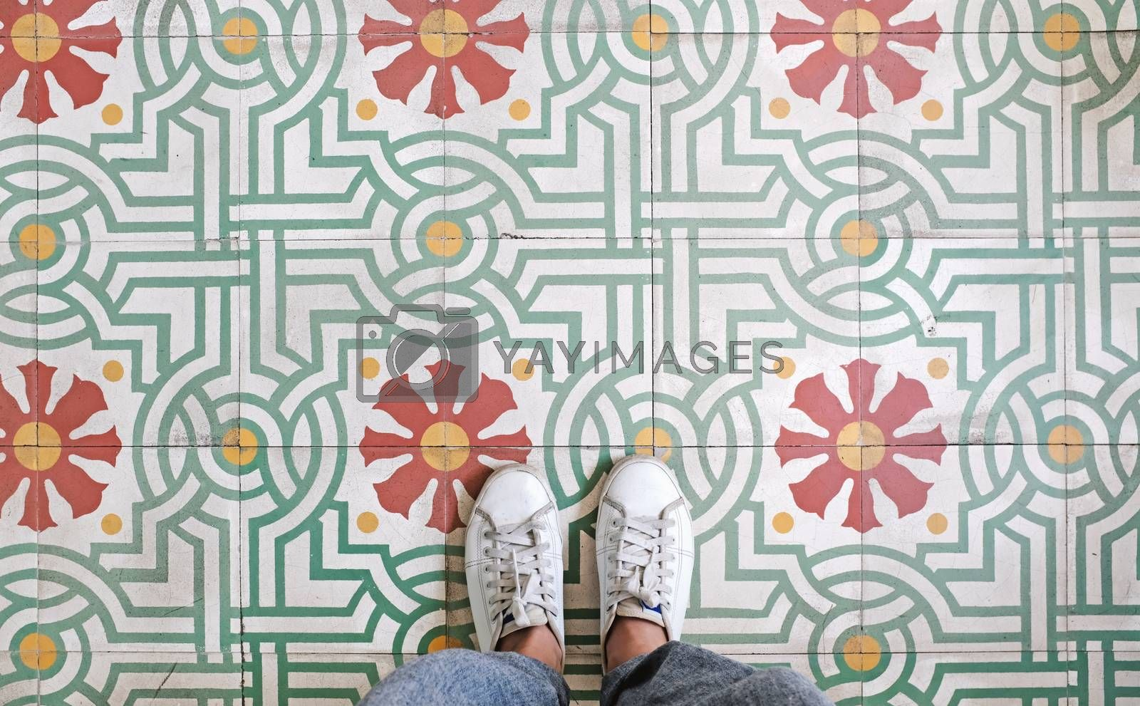 Top view selfie of feet in sneakers shoes on the vintage seamless floor background with copy space