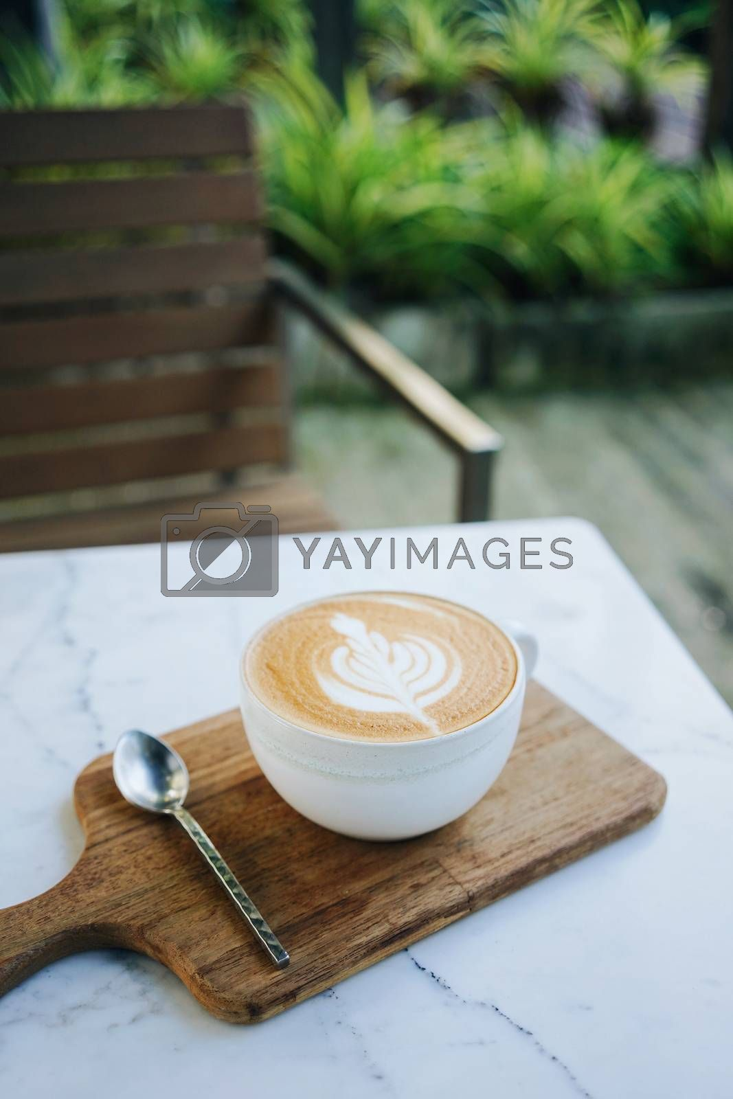 Hot cup of latte art coffee serve on the wooden tray with spoon in the garden