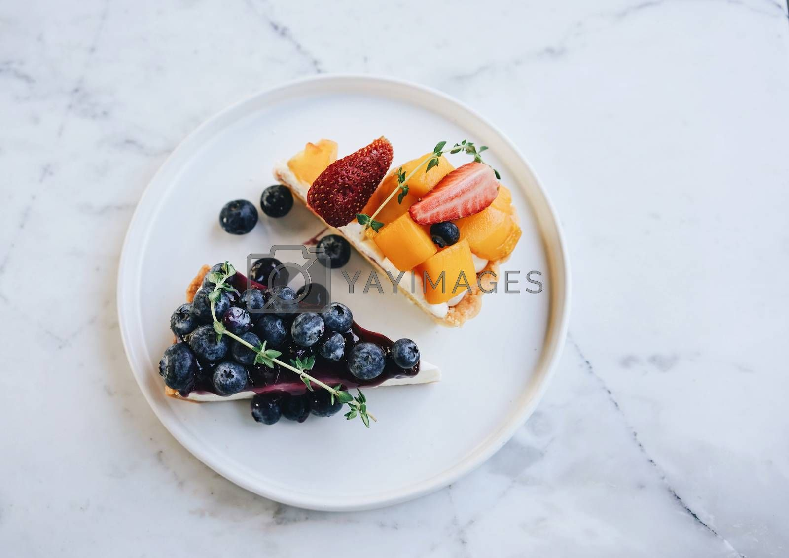 Tasty blueberry pie and mango with strawberry tart on white marble table background, homemade bakery style