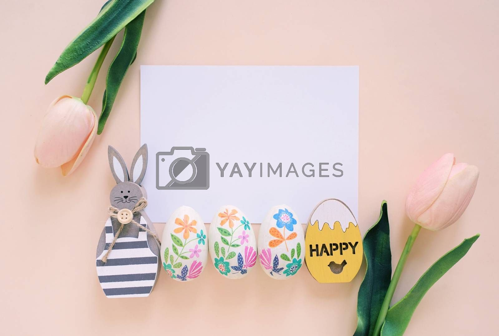 Happy Easter concept with blank card, wooden bunny, colorful easter eggs and pink tulips. Top view with copy space