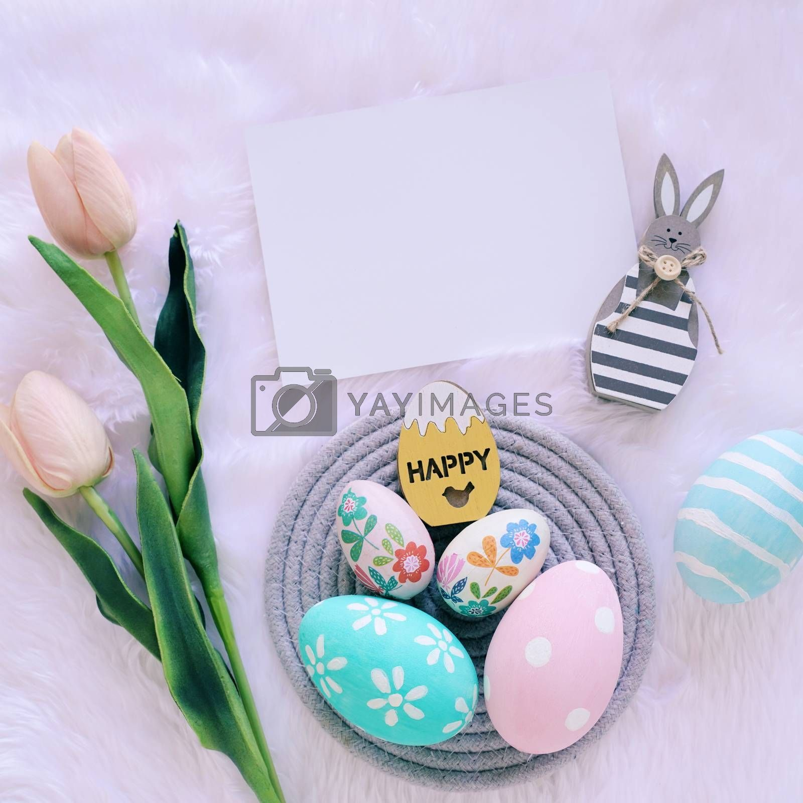 Happy Easter concept with wooden bunny and colorful easter eggs on white fur background and pink tulips. Top view