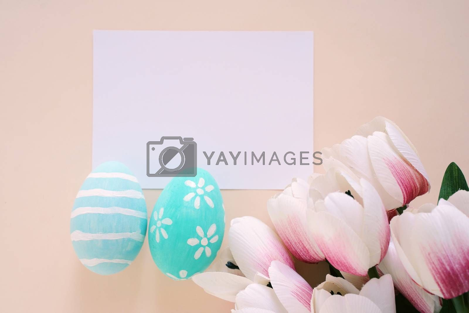 Happy Easter concept with blank card, colorful easter eggs and pink tulips. Top view with copy space