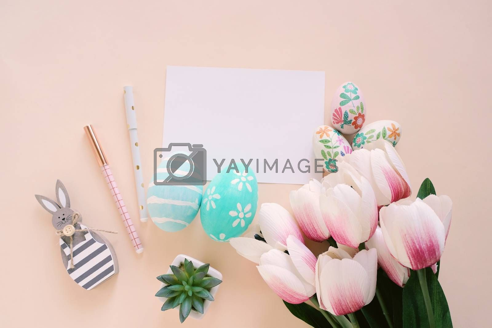 Happy Easter concept with blank card and colorful easter eggs and pink tulips. Top view with copy space