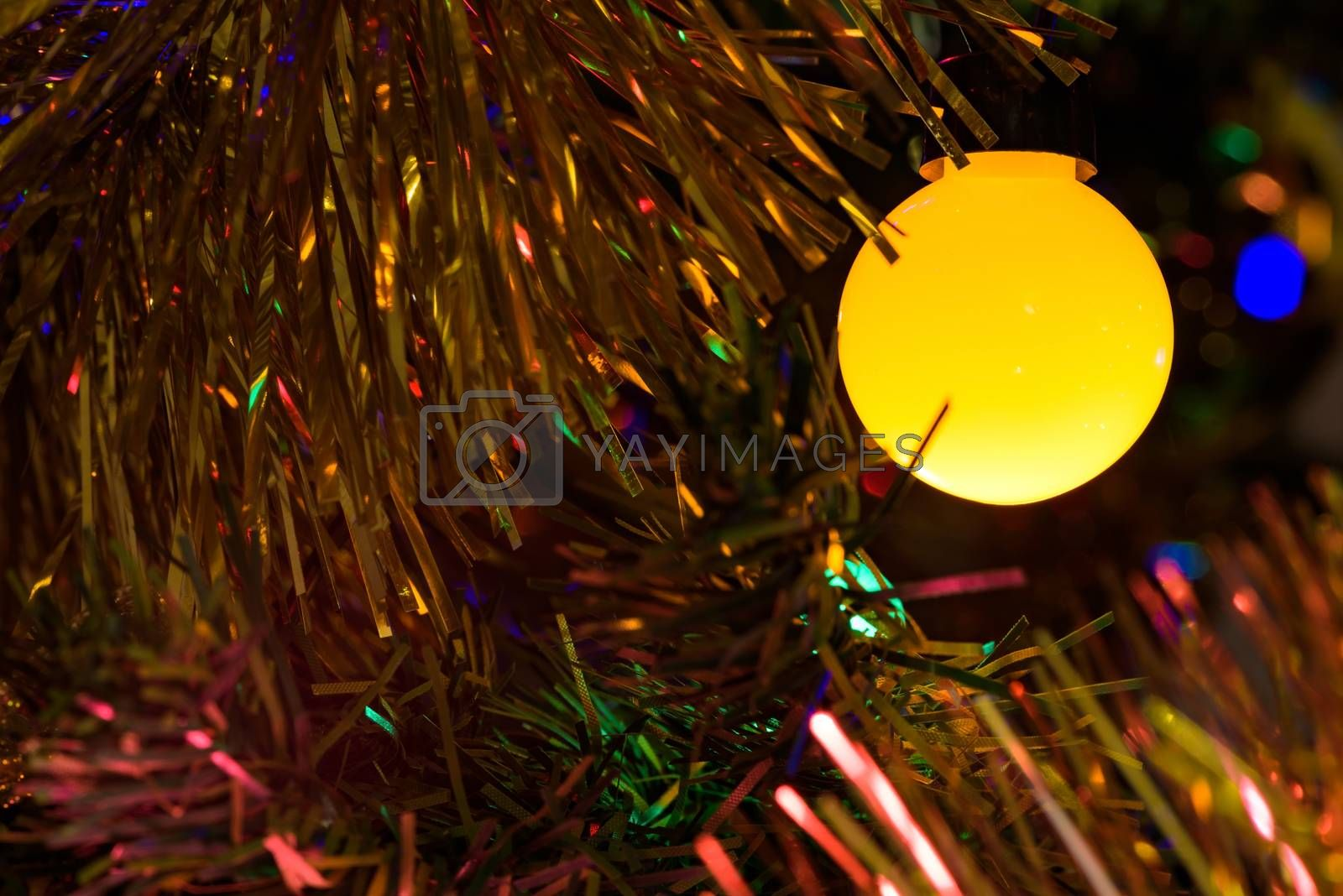 Closeup of yellow Christmas tree lamp as background