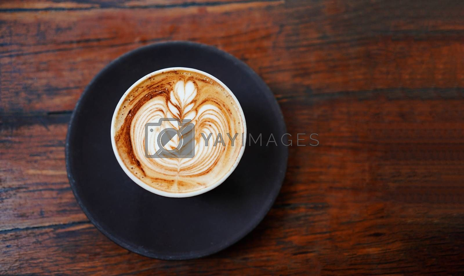 Royalty free image of Top view of hot latte or cappuccino coffee on rustic wooden tabl by nuchylee