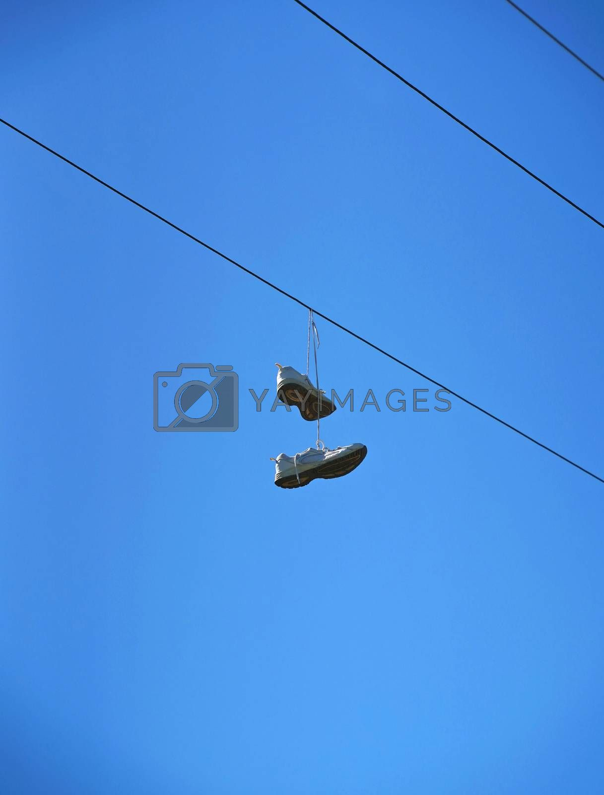Royalty free image of Old sneaker shoes hanging on an electric cable against blue sky by nuchylee