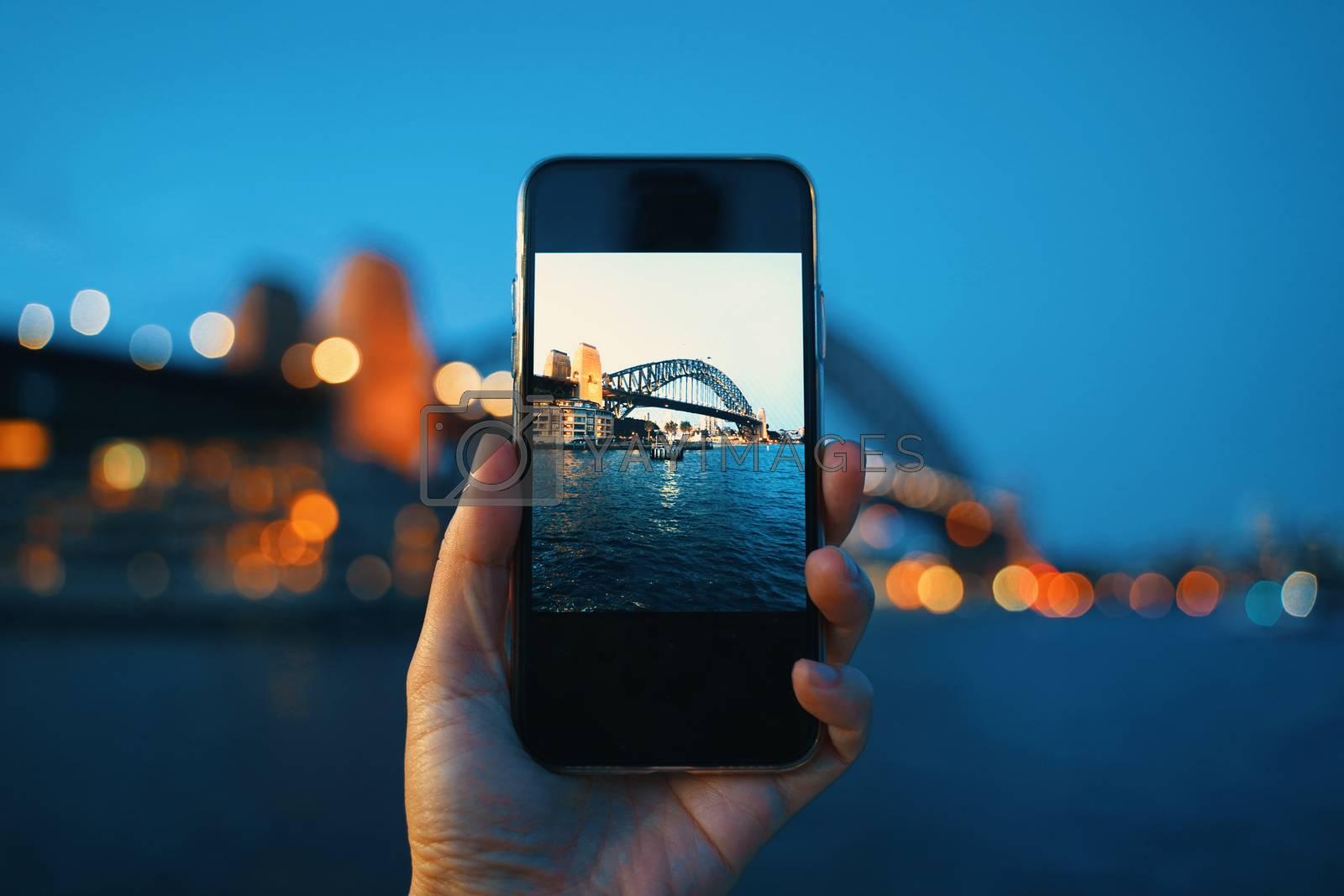 Hand holding smartphone screen taking photo of Sydney Harbour Bridge at night, Sydney in Australia